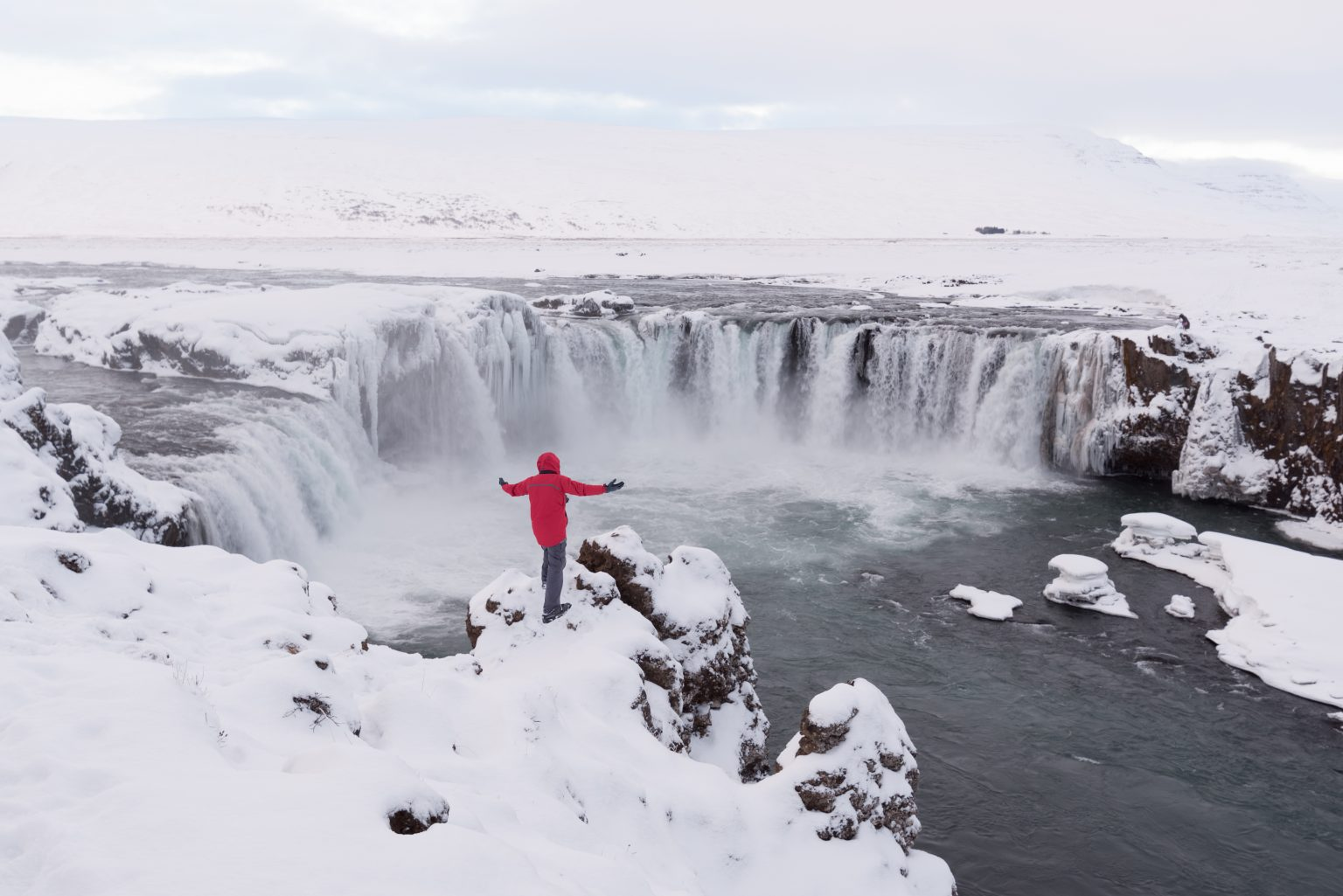 man in red standing in front of godafoss
