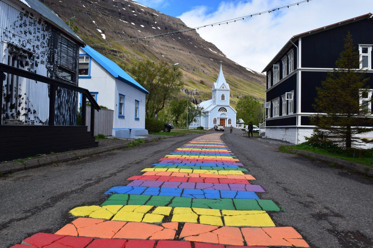 blue church and rainbow road in Seydisfjordur