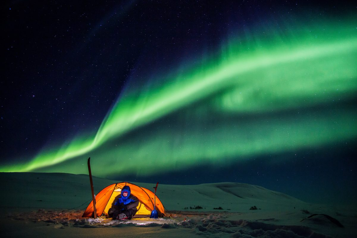 Camping in a tent with the northern lights above.