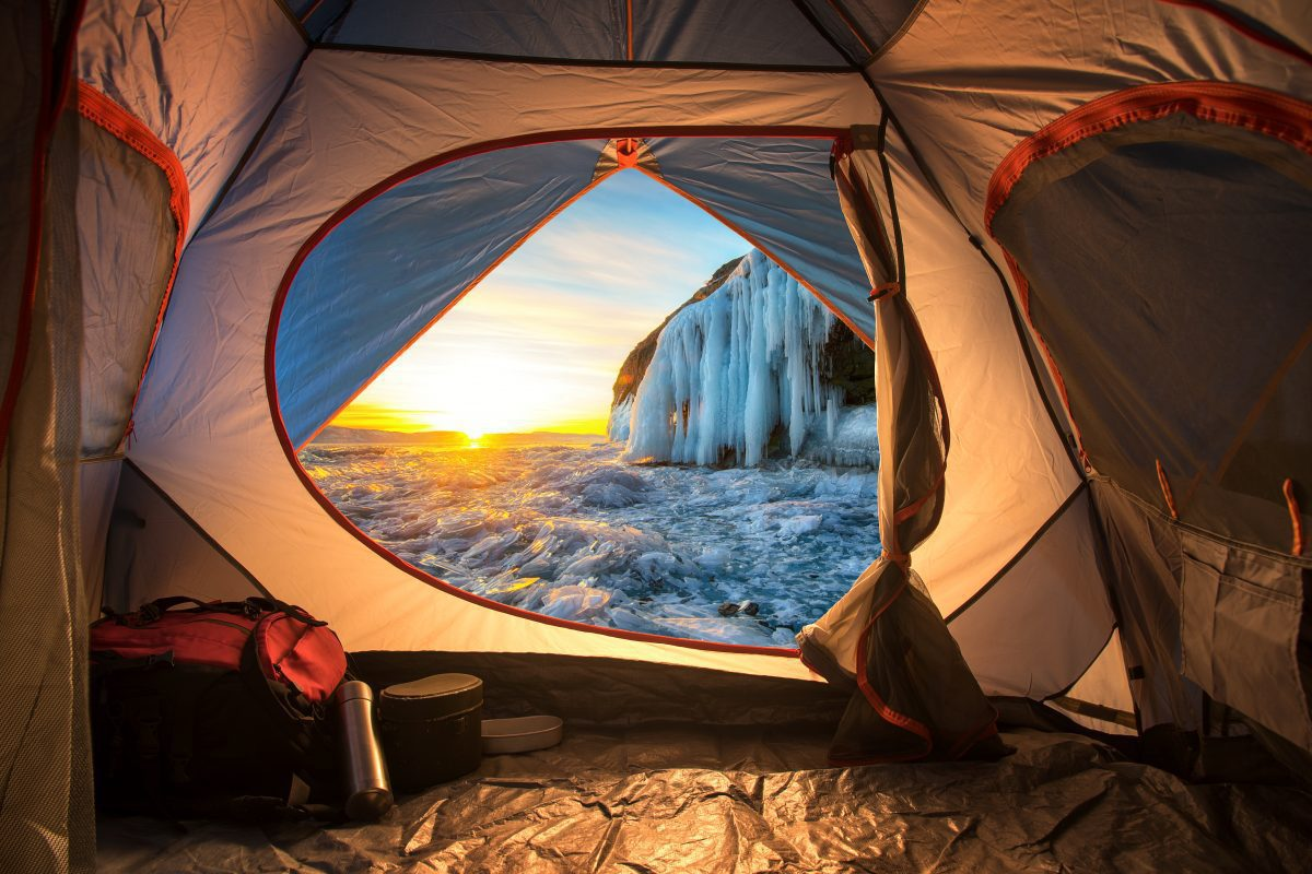 Camping in a tent next to a frozen waterfall
