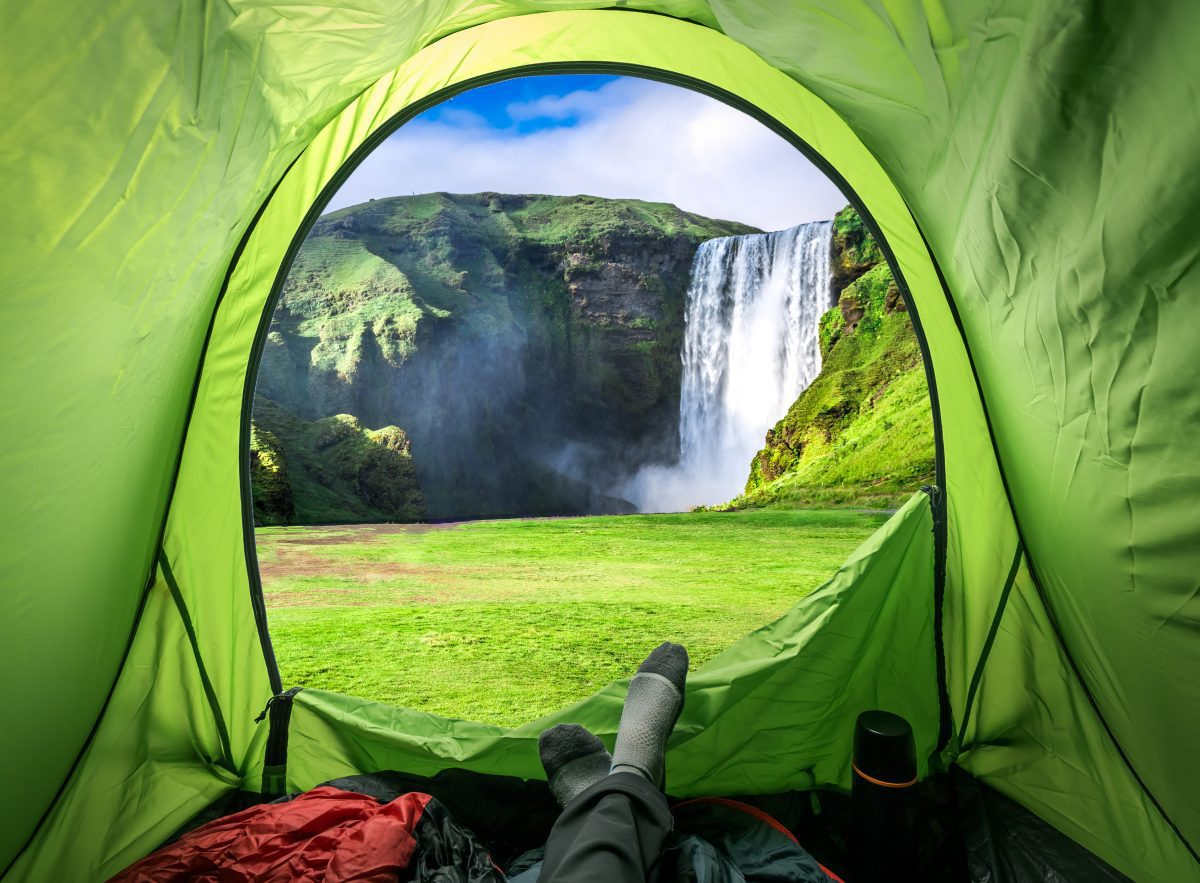 Tourist admiring Skógafoss Waterfall from the comfort of his tent.