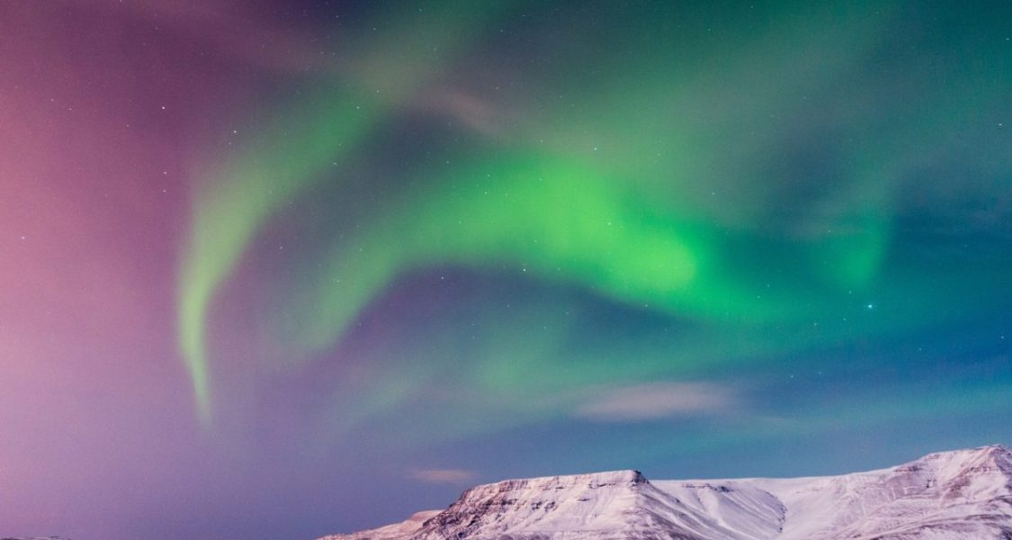 northern lights over snow covered fjords in icleand