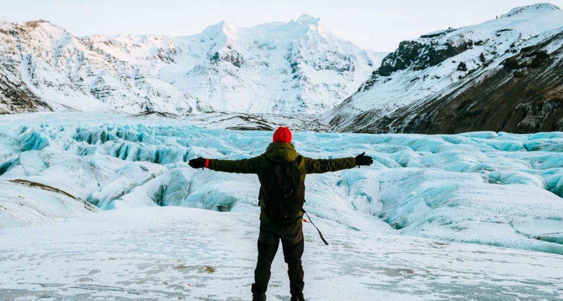 hiker standing in front of a glacier in iceland