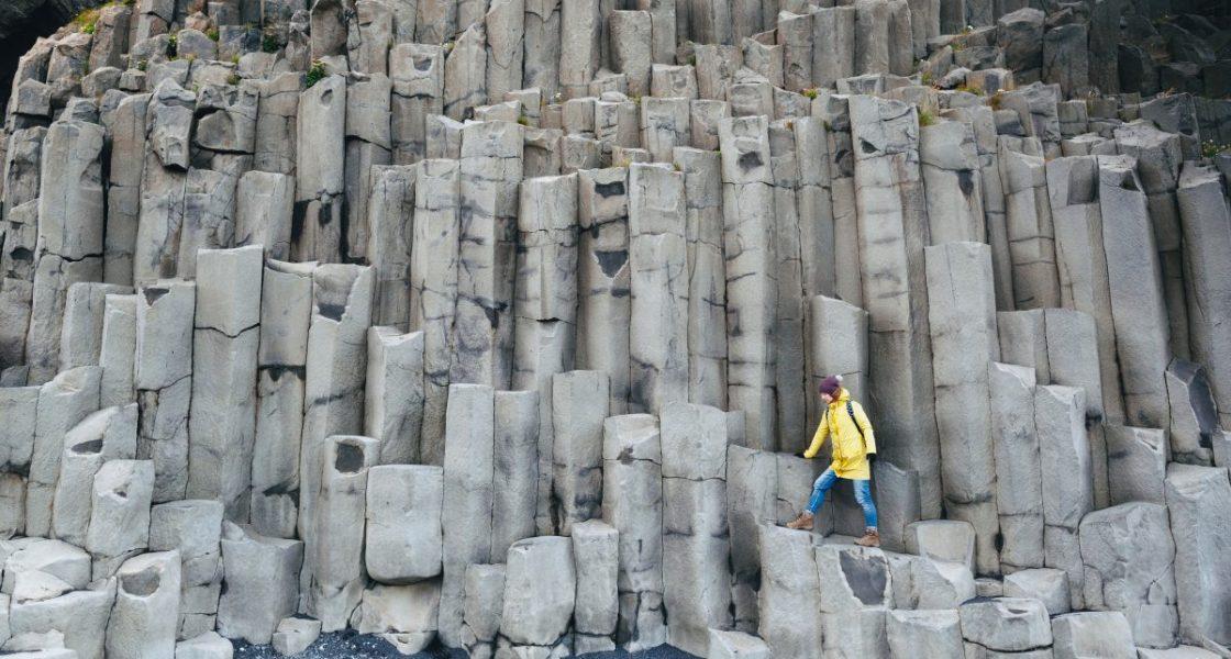 Femme marchant sur des colonnes de basalte en Islande