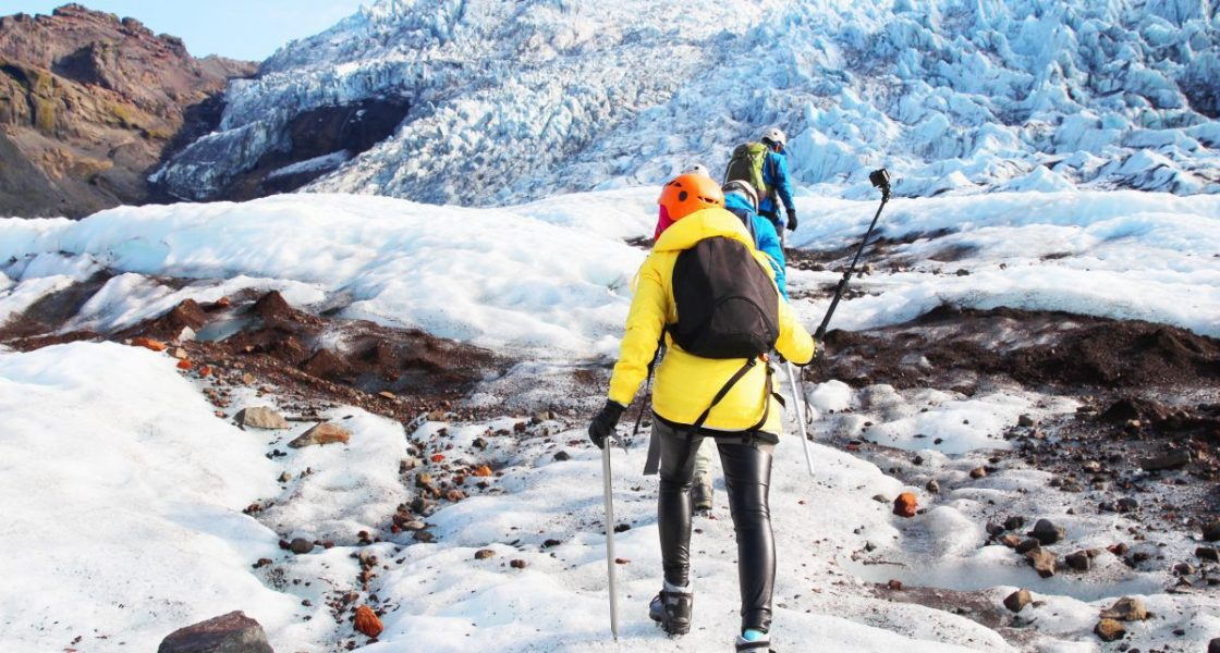 hikers walk on a glacier in iceland